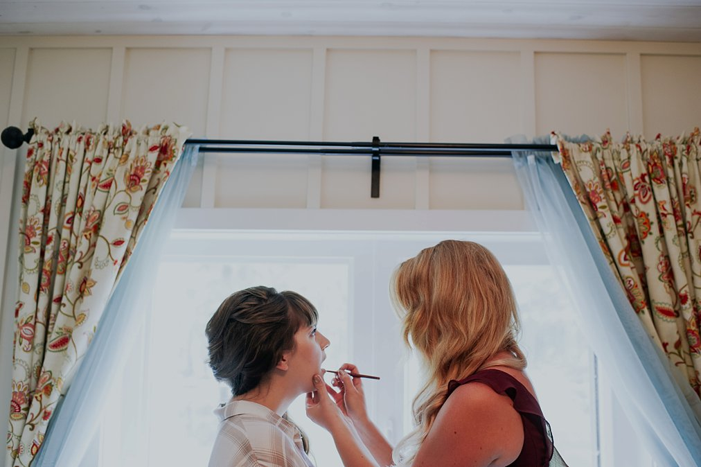 bride getting make up done in a cabin