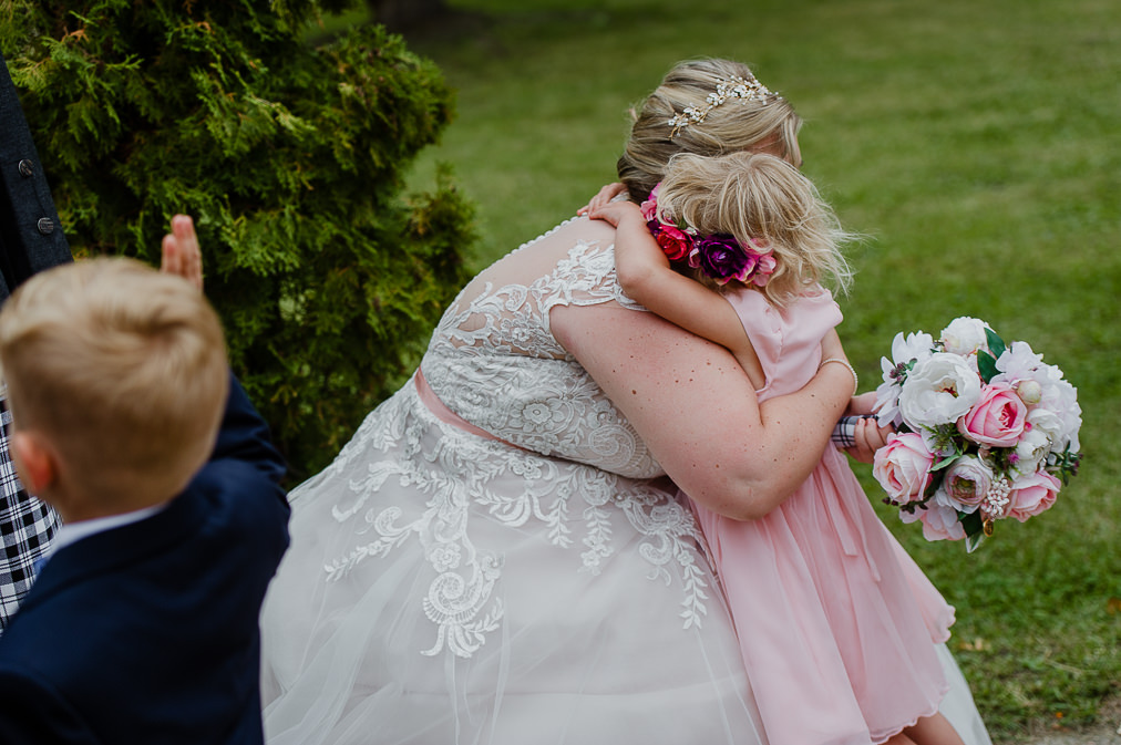 candid moment with flower girl hugging bride